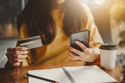 young-beautiful-asian-woman-using-smart-phone-and-credit-card-for-shopping-online-in
