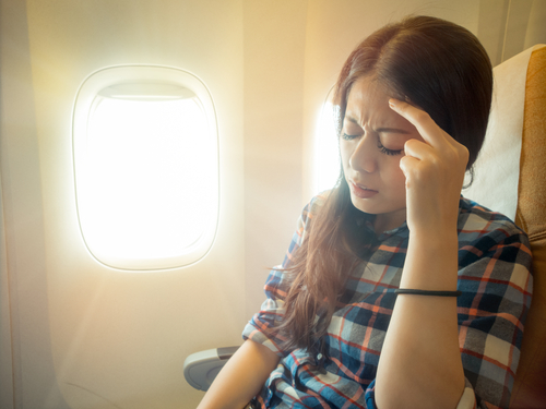 woman in airplane headache