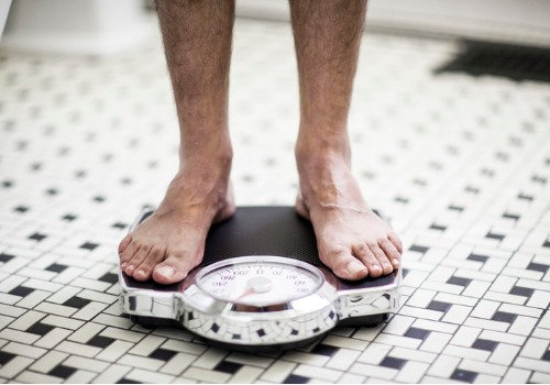 adult-man-on-bathroom-scales-aia-malaysia.jpg