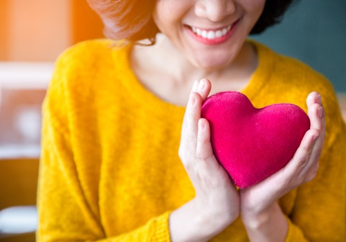 woman-hands-in-yellow-sweater-holding-pink-heart-aia-malaysia