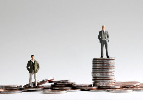 miniature-people-standing-on-a-pile-of-coins